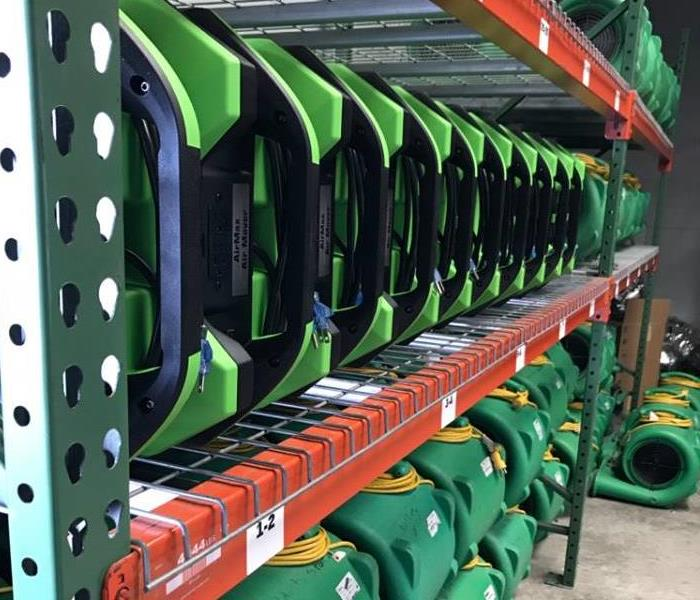 green equipment lined up on warehouse shelving